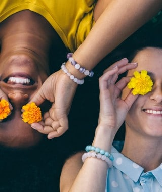Two girls laying down smiling, and placing flowers over their eyes.