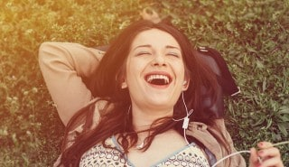 Woman with straight black hair, laying on the green grass with headphones