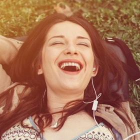 A girl enjoying music on the grass with one hand behind her head.