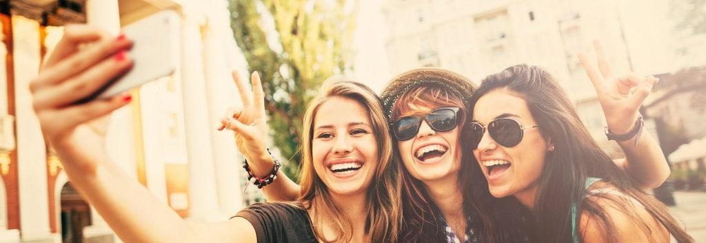 ثلاث فتيات يقمن بالتقاط صورة والابتسامة تزين وجوههن