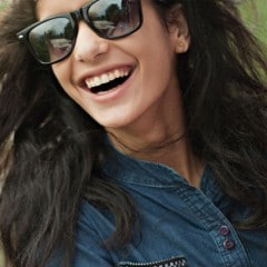 A girl wearing sunglasses and laughing.