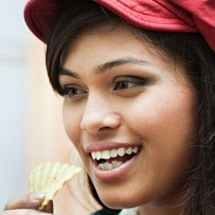 close up of a woman eating crisps and wearing a red trucker hat.