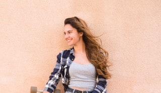 Happy woman with smooth long hair holding a skateboard and leaning against a wall.