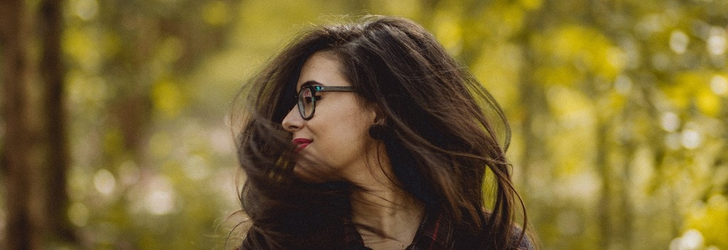 A woman with long, dark, windswept hair and wearing glasses, facing to the side.
