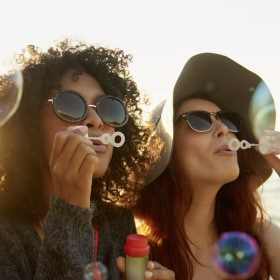 Close up of two girls blowing soap bubbles at sunset