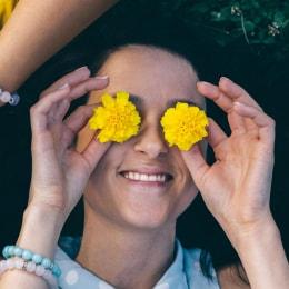 فتاة مستلقية على العشب وتقوم بوضع الأزهار على عينيها
