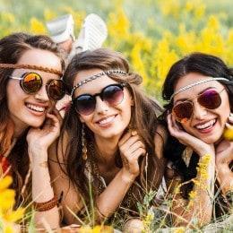 ثلاث فتيات مستلقيات فوق العشب وبين الورود